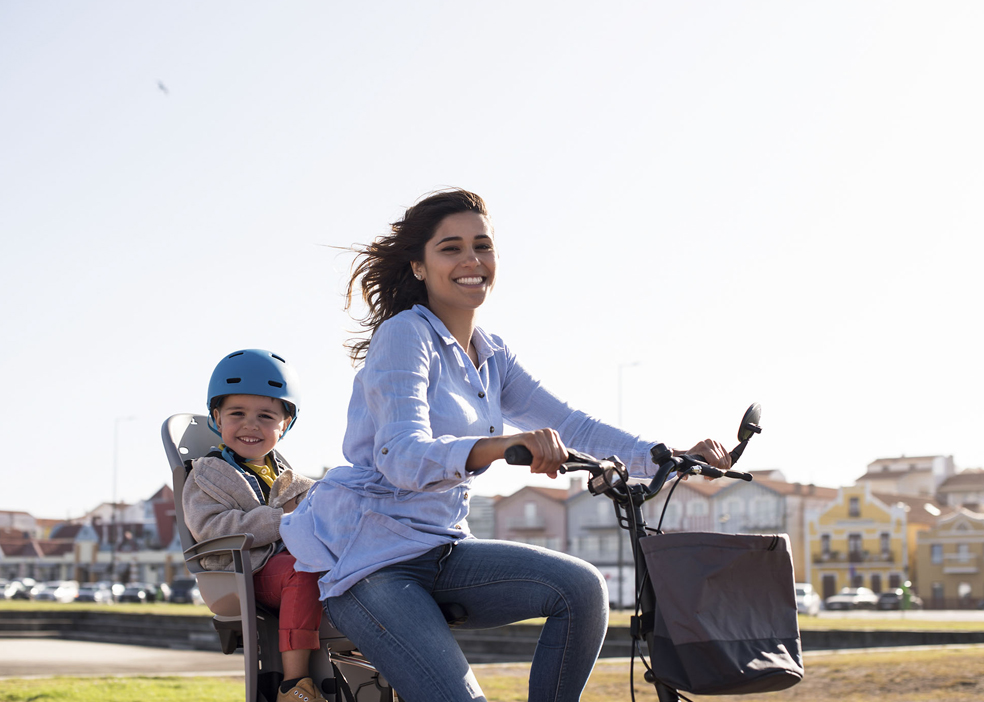 Mother riding on a bicycle with young kid