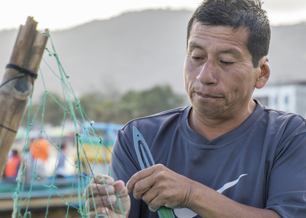 Fisherman repairs his net