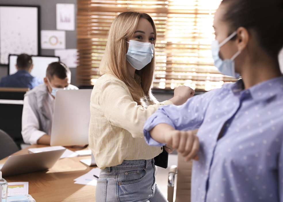 Coworkers with protective masks making elbow bump in office. Inf